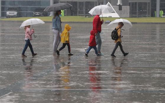 부산지방에 호우주의보가 내려진 26일 오후 부산 해운대구 벡스코를 찾은 관광객들이 우산을 쓴 채 광장을 지나고 있다. 송봉근 기자