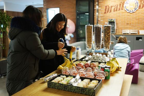 카카오게임즈는 빈속으로 출근한 직원들을 위해 김밥과 과일 등 간단한 식사류를 무료로 제공한다. 아침거리를 살펴보는 카카오게임즈 직원들. 사진 카카오게임즈