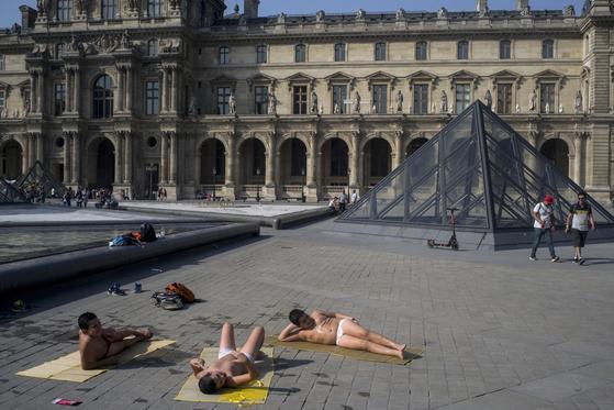 더위에 지친 시민들이 24일 파리의 루브르 박물관 (Louvre Museum) 분수대 옆에서 기록적인 더위를 피하고 있다. [(AP = 연합뉴스]