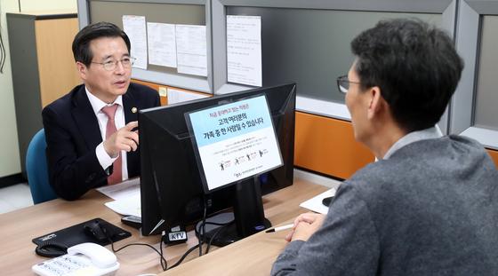 지난해 9월 김용범 금융위원회 부위원장(왼쪽)이 장기소액연체자 지원정책 현장 점검을 위해 수원시 서민금융통합지원센터를 방문해 연체자와 상담하고 있다. [뉴스1]