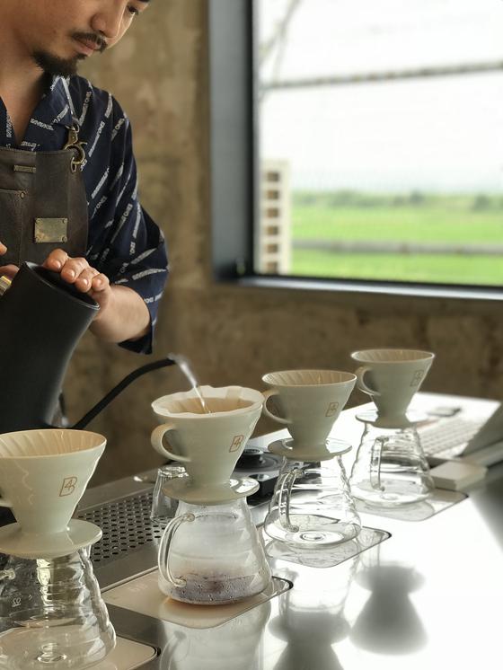 임진각에 있는 카페 포비DMZ에서 바리스타가 커피를 내리고 있다. 창밖으로 보이는 철조망의 모습이 색다르다.