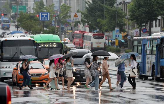 장마전선의 영향으로 전국이 흐리고 곳곳에 비가 내린 가운데 28일 서울 마포구 동교동 삼거리에서 시민들이 우산을 쓰고 발걸음을 재촉하고 있다. [뉴스1]