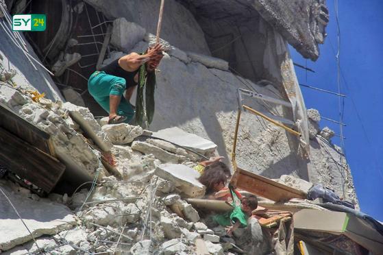 세 딸이 시리아 정부군의 폭격으로 무너진 잔해속에 깔렸다. 손을 쓸수 없는 아버지가 세 딸을 보며 절규하고 있다. 5살 리암이 7개월된 동생 투카의 옷자락을 잡고 있다.[AFP=연합뉴스]