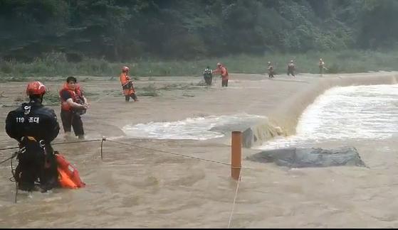 27일 정오 쯤 전북 진안군 진안읍 구량천에서 119 구조대가 폭우에 고립됐던 피서객 11명을 구조하고 있다. [전북소방본부 제공=연합뉴스]