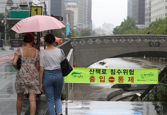 전국에 장맛비가 예보된 28일 서울 종로구 청계천 입구에서 관광객들이 출입 통제된 청계천을 지나가고 있다. [연합뉴스]