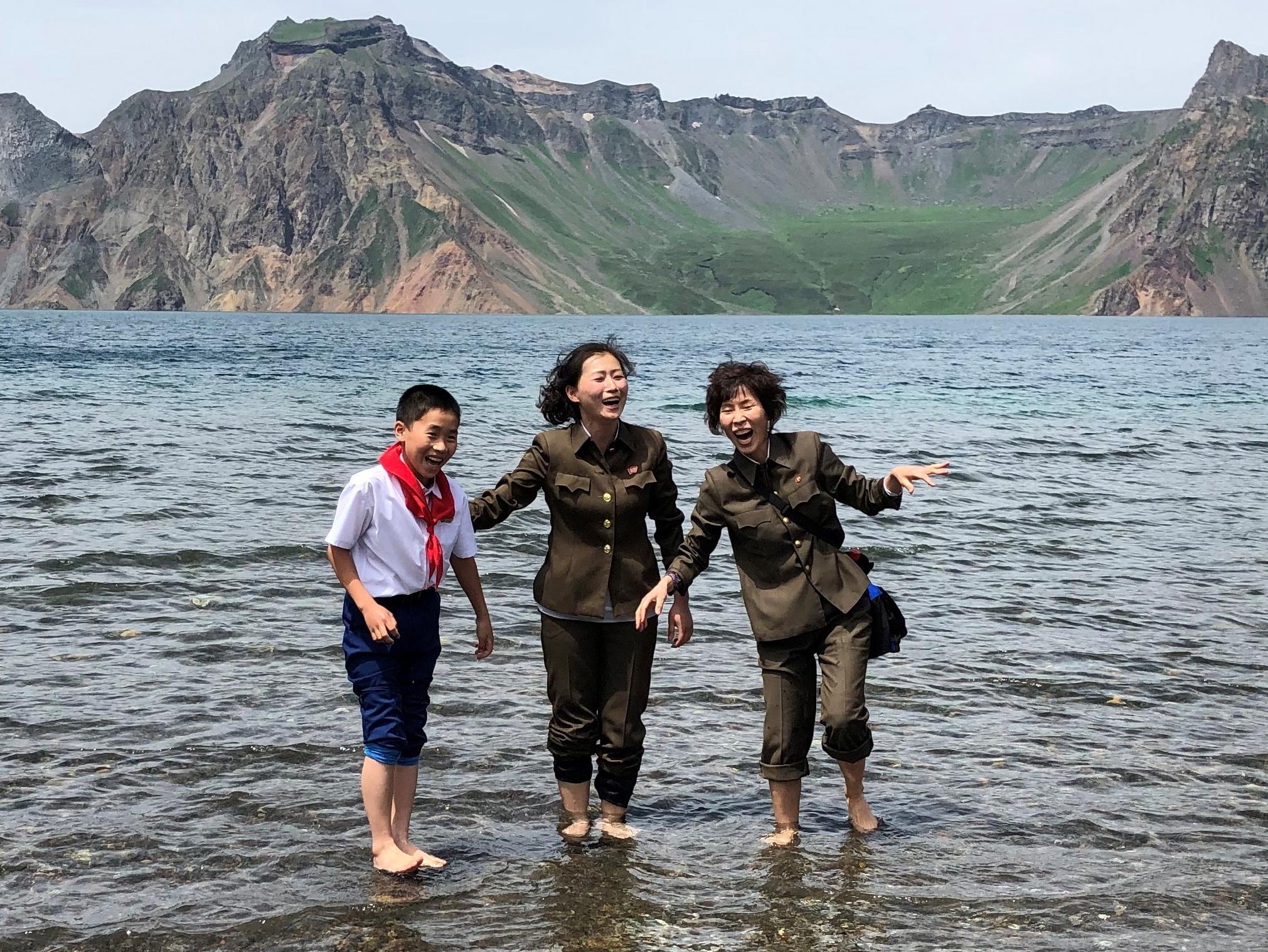 지난 24일 백두산을 방문한 관광객들이 천지에 발을 담그며 기념사진을 찍고 있다. [타스=연합뉴스]