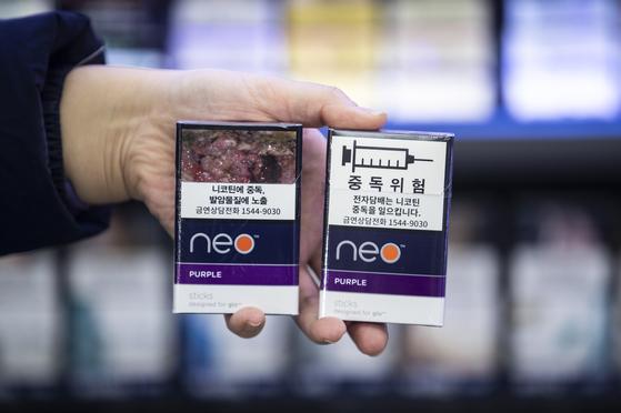 서울 종로구의 한 편의점에서 관계자가 흡연 경고그림이 변경된 전자 담뱃갑(왼쪽)과 기존 전자 담뱃갑을 들고 있다. 내년 12월에는 경고 그림과 문구가 담뱃갑 면적의 3분의 2까지 확대된다. [연합뉴스]