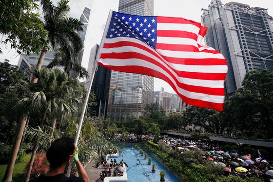 송환법을 반대하는 한 시민이 28일 홍콩 차베스 가든에서 경찰 폭력에 항의하는 행진대열을 향해 성조기를 들고 있다. [로이터=연합뉴스]