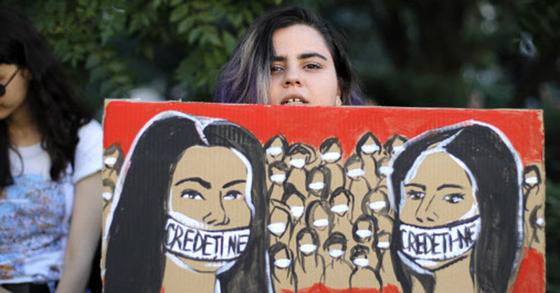 루마니아 여성이 28일(현지시간) 수도 부큐레슈티에서 열린 두 10대 여성의 납치 살해 규탄 시위 도중 '우리를 믿어달라'고 적힌 마스크를 쓴 채 침묵 시위를 하는 여성들의 그림을 들고 있다. [AP=연합뉴스]