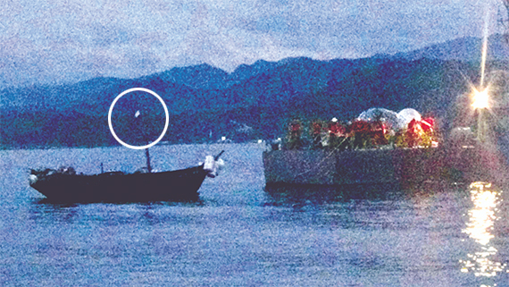 """군은 지난 27일 밤 동해 북방한계선을 넘어온 북한 목선을 예인했다. 북한 목선 마스트에 하얀 수건(원 안)이 걸려 있어 군이 귀순 의사를 물었으나 북한 선원은 '아니요. 일 없습니다""""라고 답변한 것으로 알려졌다. [연합뉴스]"""
