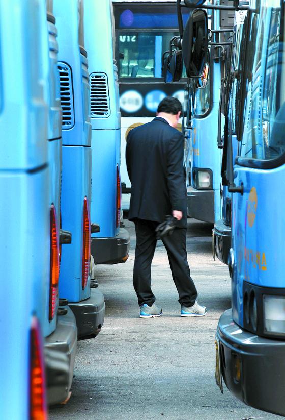 서울의 한 차고지에 주차된 버스 사이를 기사가 지나고 있다. 버스기사들은 정년이 63세까지 연장돼 일정 기간 동안 연금이 삭감되고 연금 소득세까지 무는 '이중 손실'을 겪는다. [중앙포토]