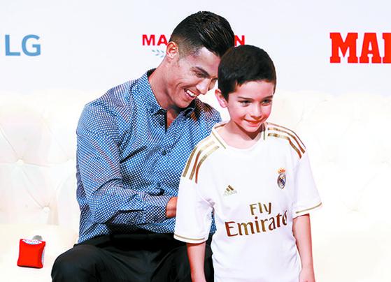 호날두가 30일 열린 스페인 매체 마르카의 레전드상 시상식에서 어린이 팬에게 사인을 해주고 있다. 26일 방한 당시 호날두는 아무런 설명 없이 사인회에 불참했다. [로이터=연합뉴스]
