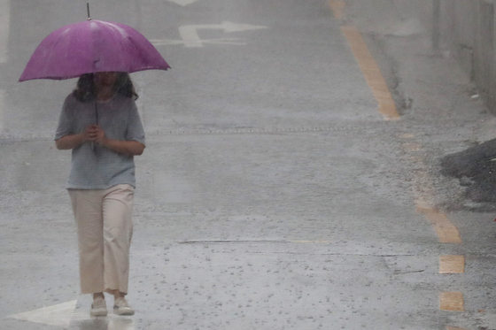 서울과 경기도, 강원 일부에 31일 아침 호우주의보가 발표됐다. 지난 25일 경기도 수원시 장안구 거리에서 한 시민이 우산을 쓴 채 발걸음을 재촉하고 있다. [뉴스1]