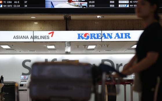 아시아나항공이 대한항공에 이어 오는 9월부터 기종 변경을 통해 일본 노선 공급 조정에 들어간다. 기존 비행기를 소형기로 대체해 좌석수를 줄이는 방식이다. 전날 대한항공은 9월부터 부산~삿포로 노선의 운항을 중단한다고 밝힌 바 있다. 앞서 일본 노선 조정을 결정한 저비용항공사(LCC)들에 이어 대형항공사(FSC)도 잇따라 노선 공급조정에 나서며 항공업계에서 일본 노선 수요 감소 여파가 가시화되고 있다. 사진은 김포공항 내 대한항공, 아시아나항공. [뉴스1]