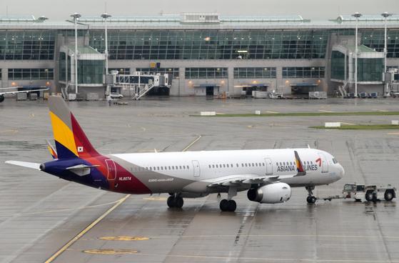 한국에 대한 일본의 수출규제로 촉발된 일본여행 거부 운동이 확산하면서 아시아나항공은 9월 중순부터 인천발 후쿠오카·오사카·오키나와 노선 투입 항공기를 기존 A330에서 B767·A321 등으로 변경해 좌석 공급을 축소할 예정이다.   사진은 31일 오전 인천국제공항 계류장에 있는 아시아나항공 여객기 모습. [연합뉴스]