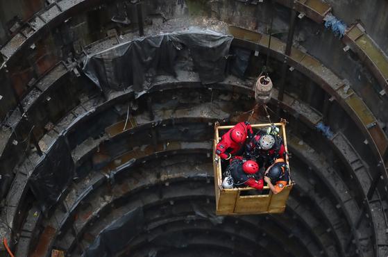 지난달 31일 갑작스런 폭우로 작업자들이 고립된 서울 양천구 목동 빗물 펌프장에서 구조대원들이 수색작업을 위해 크레인을 이용해 사고 현장으로 이동하고 있다. [연합뉴스]