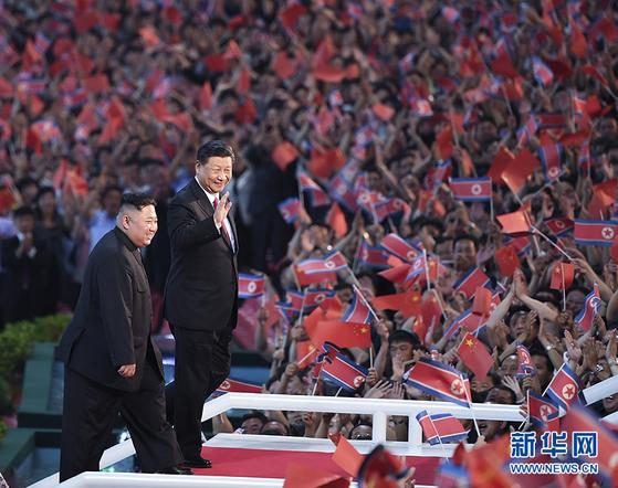 시진핑 중국 국가주석이 김정은 북한 국무위원장과 함께 6월 20일 평양 5.1 경기장에 운집한 10만 북한 관중을 향해 손을 흔들어 인사하고 있다. [중국 신화망]