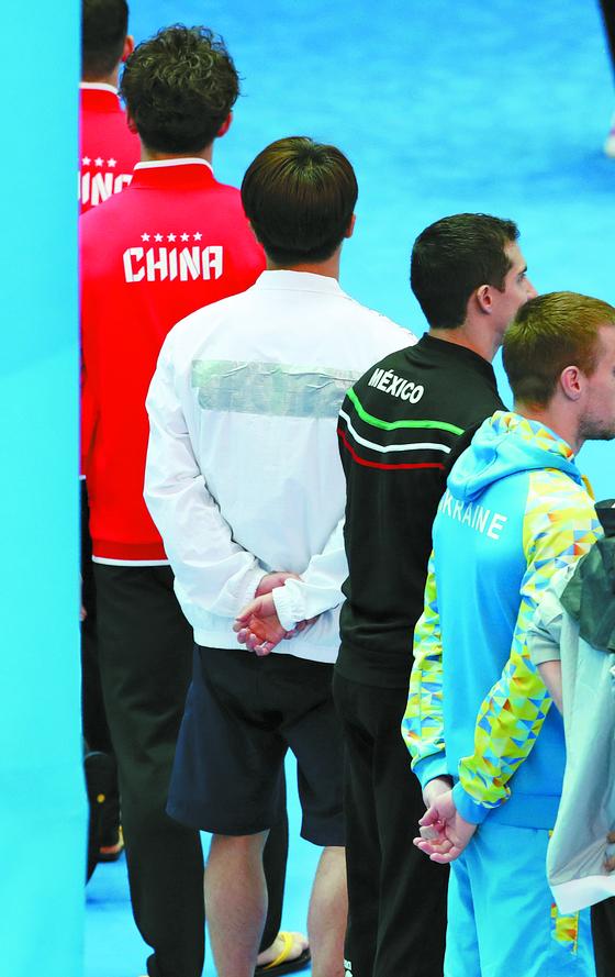 7월 14일 오후 광주 광산구 남부대학교 시립국제수영장에서 열린 2019 광주세계수영선수권대회 남자 1m 스프링보드 결승경기에 출전하는 한국의 우하람(왼쪽 세번째)이 각국 선수들과 입장을 마치고 퇴장하고 있는 가운데 우하람 상의 트레이닝복 뒤가 테이프로 가려져 있다. [뉴시스]