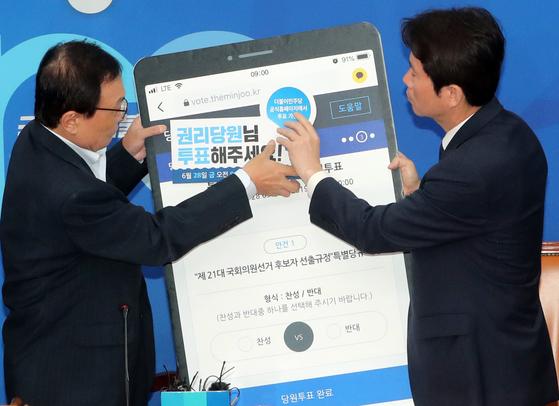 이해찬 더불어민주당 대표와 이인영 원내대표가 지난 6월 28일 서울 여의도 국회에서 열린 최고위원회의에서 '권리당원투표'를 홍보하는 피켓을 들고 있다. 더불어민주당은 '제21대 총선 공천 규정을 확정하기 위해 28일부터 이틀간 권리당원들을 대상으로 한 인터넷 투표를 했다. [뉴스1]