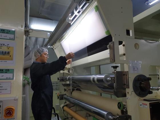 SR테크노팩 직원이 이 회사의 고차단 필름을 살펴보고 있다. 이 필름은 즉석밥 등 식품용 포장용기에 쓰인다. 그간 전량 일본산 소재에 의존하던 것을 최근 국산화에 성공했다. [사진 SR테크노팩]