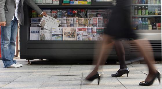 신문은 지하철과 편의점에서 흔히 팔았지만, 요즘엔 발품을 팔아야 살 수 있다. 기술이 발전해 디지털화되면서 정보를 찾는 방법이 많이 달라진 탓이다. 기술의 진보로 달라진 것은 당구장도 마찬가지다. 당구장에도 디지털 물결이 들어와, 풍경이 예전과 많이 다르다. [중앙포토]