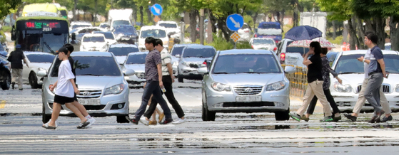 전국 대부분 지역에 폭염특보가 발효중인 2일 오후 전북 전주시 홍산로에서 시민들이 아지랑이가 피어오르는 길을 건너고 있다. [뉴스1]