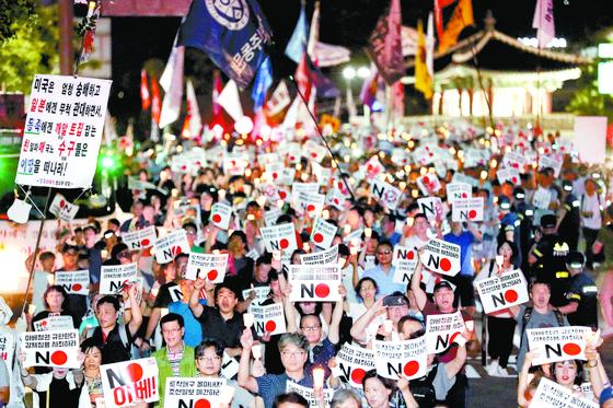 3일 저녁 서울 종로구 일본대사관 앞에서 아베규탄 시민행동 주최로 열린 '역사왜곡, 경제침략, 평화위협 아베정권 규탄 3차 촛불문화제'에서 참가자들이 촛불을 들고 행진하고 있다. [연합뉴스]
