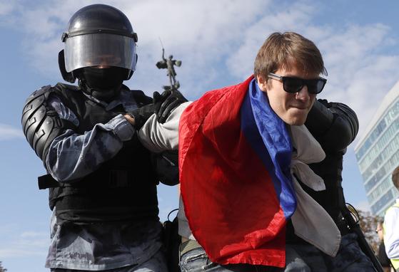 지난 3일 러시아 모스코바에서 열린 거리행진 시위에 참석한 시위대를 러시아 경찰이 붙잡고 있다. [AP=연합뉴스]