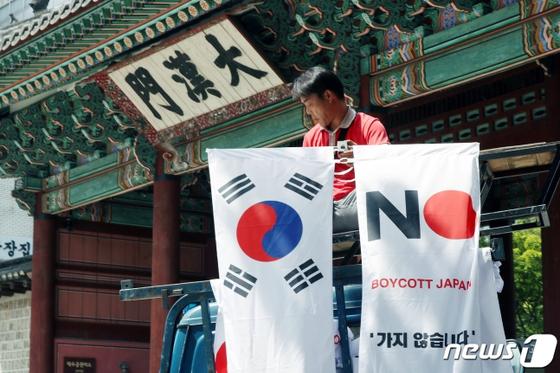 6일 오전 서울 중구 대한문 앞에서 중구청 관계자들이 태극기와 '노 재팬' 배너깃발을 설치하고 있다. [뉴시스]