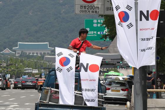 [뉴스1] 6일 오전 서울 세종대로 일대에서 중구청 관계자들이 태극기와 '노 재팬' 배너를 설치하고 있다.