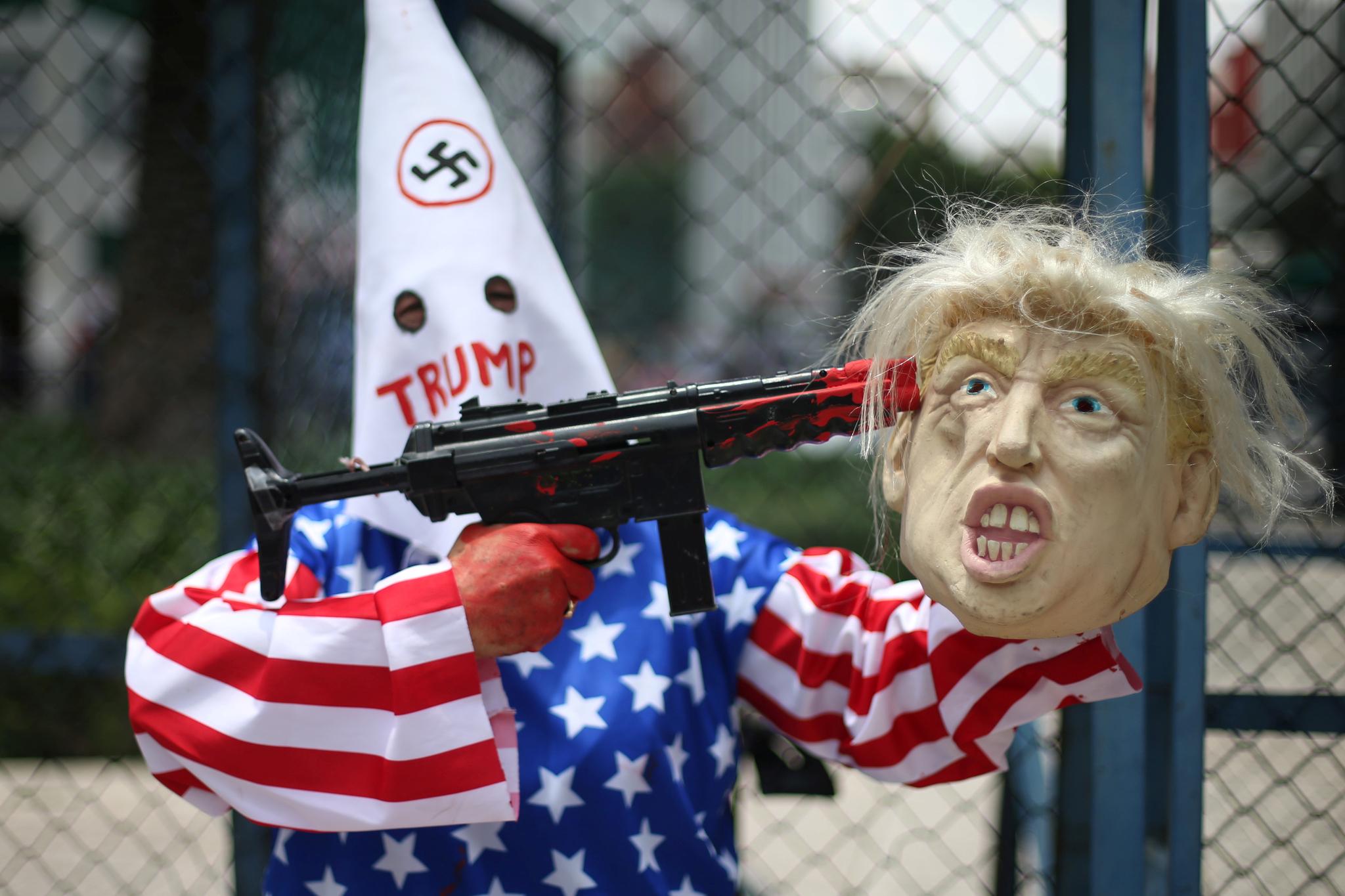 한 멕시코 시민이 6일(현지시간) 멕시코시티 미국 대사관 앞에서 엘패소 총기사고에 항의하며 장난감 총으로 트럼프 대통령을 겨누고 있다. 엘패소에선 한 백인 남성이 쇼핑몰에서 총기를 난사해 멕시코인 8명을 포함해 22명이 숨지고 24명이 다쳤다. [로이터=연합뉴스]