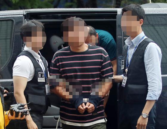 윤소하 정의당 원내대표실에 협박 소포를 보낸 혐의로 체포된 유모 서울대학생진보연합 운영위원장(가운데)이 영장실질심사를 받기 위해 지난달 31일 오전 서울 남부지방법원으로 들어서고 있다. [연합뉴스]