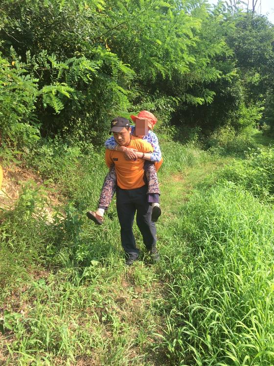 경북 김천소방서 최호 구조대원이 실종된 90대 노인을 23시간만에 구조한 뒤 업고 산을 내려오고 있다. [사진 김천소방서]
