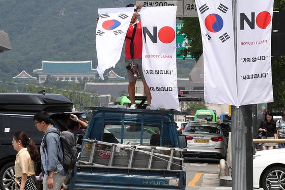 지난 6일 오전 서울 중구 세종대로 일대에서 중구청 관계자들이 태극기와 '노 재팬' 배너깃발을 설치하고 있다. [뉴스1]