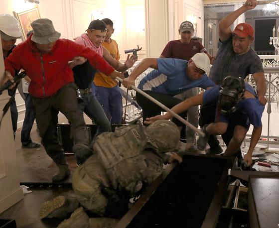 키르키스스탄 특수부대원이 7일(현지시간) 아탐바예프 전 대통령 체포 작전 중 총과 각목으로 무장한 그의 지지자들로 부터 폭행을 당하고 있다. [EPA=연합뉴스]