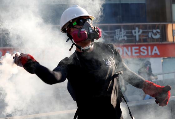 지난 5일 홍콩에서 벌어진 시위에서 검은 옷을 입은 사람이 '민주 개혁'을 주장하며 경찰을 향해 최루가스통을 되던지고 있다. [로이터=연합뉴스]