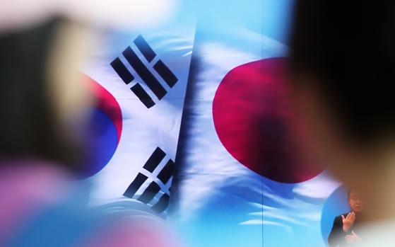 일본이 한국을 전략물자 수출심사 우대국(화이트리스트)에서 제외하는 수출무역관리령 개정안을 처리한 2일 서울 중구 서울역 대합실에서 시민들이 뉴스 속보를 지켜보고 있다. [뉴스1]