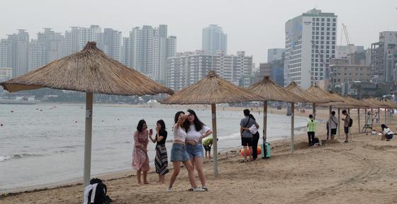 부산 수영구 광안리해수욕장이 전면 개장한 지난달 1일 장맛비로 인해 바다를 찾은 피서객들이 파라솔 아래에서 비를 피하고 있다. 송봉근 기자