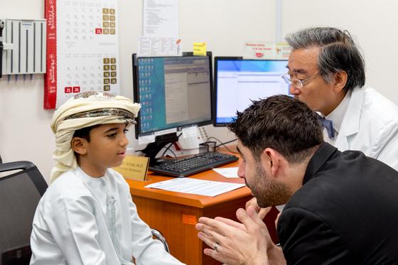 아랍에미리트 왕립병원(SKSH)에서 황용승 소아신경과 교수(오른쪽)가 어린이 환자를 진료하고 있다. 가운데는 통역 직원 칼리드. [사진 서울대병원]