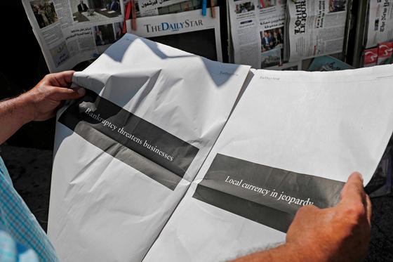 8 일 레바논 수도 베이루트에서 한 독자가 레바논 유일한 영어신문인 '데일리 스타 (Daily Star)'를 펼쳐 보고 있다. [AFP=연합뉴스]