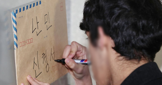 지난해 2월 이란 난민 소년이 아버지의 난민 인정 재신청서를 작성하고 있다. [연합뉴스]