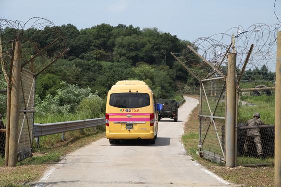 탐방객을 태운 버스가 통문을 열고 DMZ 안쪽으로 들어가는 모습. 군용 차량이 앞뒤에서 호위한다. 최승표 기자