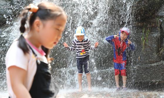 전국에 폭염특보가 내린 4일 경기도 관악산 계곡을 찾은 어린이가 떨어지는 폭포에서 더위를 식히고 있다. 우상조 기자