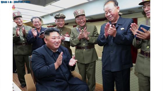 """북한 조선중앙TV가 11일 전날 함경남도 함흥 일대에서 실시한 2발의 단거리 발사체 발사 장면을 사진으로 공개했다. 북한 매체들은 김 위원장이 """"새로운 무기가 나오게 되었다고 못내 기뻐하시며 커다란 만족을 표시하시였다""""고 전했다. 사진은 김 위원장이 수행 간부들과 발사를 마친 뒤 박수를 치고 있는 것으로 보인다. 연합뉴스"""