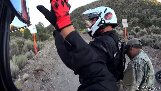 51구역 외곽 경계를 맡은 민간 경비회사 무장 경비원이 무단침입한 오토바이 운전자의 몸을 수색하고 있다. 이런 무단침입자는 링컨 카운티 보안관에게 넘겨진다.  [사진 유튜브 MACADVENTURES 계정 캡처]