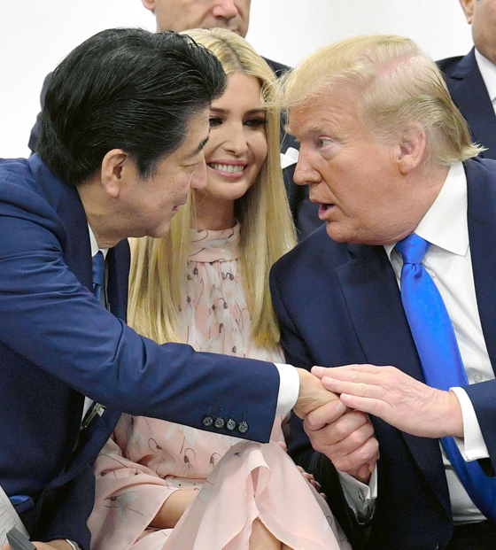 아베 신조(安倍晋三) 일본 총리(왼쪽)과 도널드 트럼프 미국 대통령(오른쪽)이 지난달 일본 오사카에서 열린 주요 20개국(G20) 정상회의의 특별 세션에서 트럼프 대통령의 딸 이방카를 사이에 두고 서로 손을 잡으며 대화를 나누고 있다. [연합뉴스]