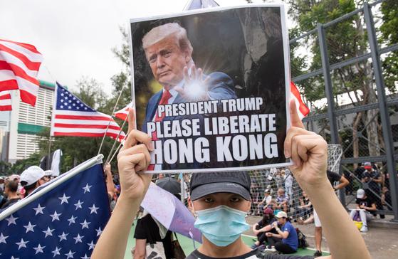 11일 홍콩 빅토리아 공원에서 진행된 송환법 반대시위에서 한 참가자가 도널드 트럼프 미국 대통령의 사진을 들고 있다. [EPA=연합뉴스]