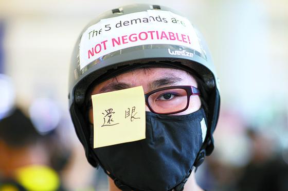 12일 홍콩 시위대가 경찰이 쏜 고무탄에 맞아 한 여성 시위자의 안구가 파손된 사건에 항의하기 위해 자신의 눈에 '안구를 돌려달라'는 내용의 포스트잇을 붙였다. [EPA=연합뉴스]