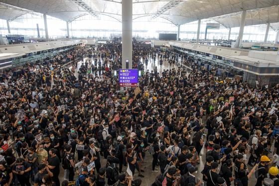 '범죄인 인도 법안'(송환법)에 반대하는 홍콩 시위대가 12일 홍콩 국제공항 출국장에 모여 시위를 벌이고 있다. 이날 수천 명의 시위대가 홍콩 국제공항에 몰려 연좌시위를 벌이면서 여객기 운항이 전면 중단됐다. [연합뉴스]