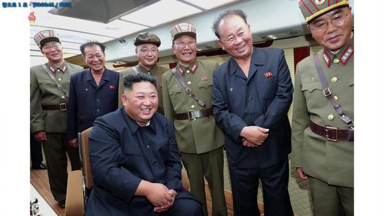 김정은 북한 국무위원장이 지난 10일 수행원과 단거리 발사체 발사 장면을 보고 있다. [조선중앙TV=연합뉴스]